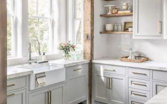 kitchen, dark wooden floor, white wall tiles, white cabinet, wooden floating shelves, white marble counter top, white apron sink, wooden beam frame, white frame windows,