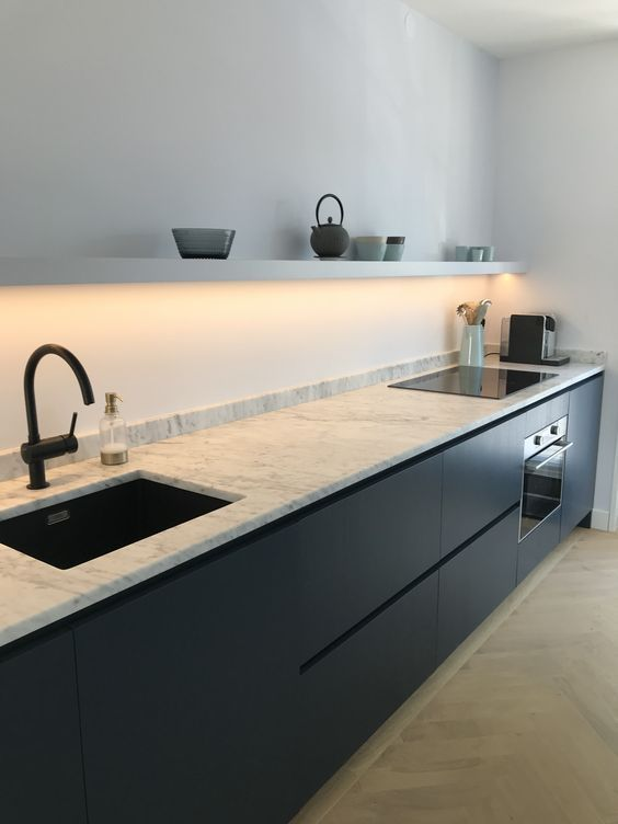 kitchen, light brown chevron floor tiles, white wall, white floating shelves, black cabinet with matble top, black faucet