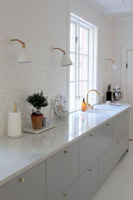 kitchen, white floor, white subway wall tiles, white counter top, off white bottom cabinet, white sconces.