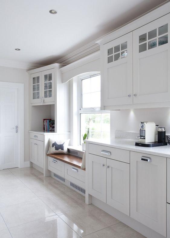 kitchen, white marble floor, white cabinet, white backsplash, white framed window, wooden bench