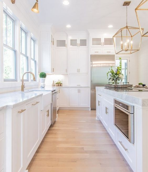 kitchen, white wall, wooden floor, white bottom cabinet, white counter top, golden cage pendant, golden sconces, glass window
