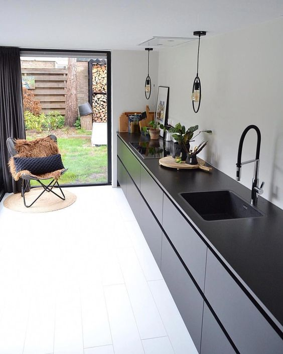 kitchen, white wooden floor, black bottom cabinet with black counter top, pendants, white wall, black framed large windows, black butterfly chair