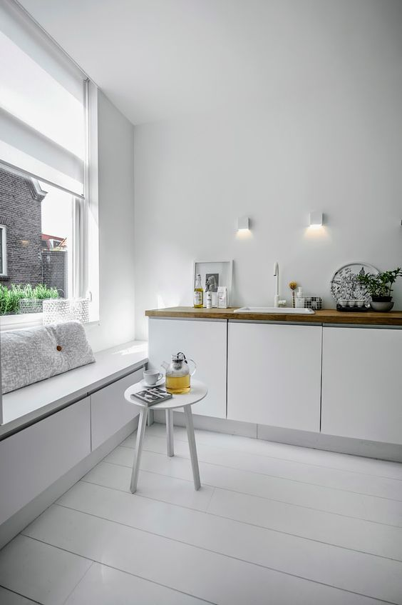 kitchen, white wooden floor, white wall, white bottom cabinet with wooden counter top, white bench with drawers, large window