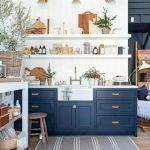 Kitchen, Wooden Floor, Dark Blue Bottom Cabinet, White Shiplap Wall, White Counter Top, White Apron Sink, White Shelves, Golden Sconces