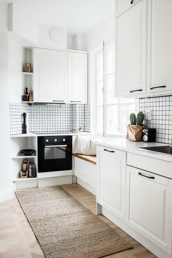kitchen, wooden floor, white cabinet, white black backsplash, window seat