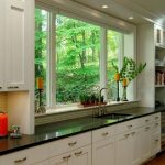 Kitchen, Wooden Floor, White Wall, White Ceiling, White Bottom Cabinet, Black Counter Top, Large Glass Window