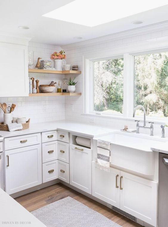 kitchen, wooden floor, white wooden wall planks, glass ceiling window, white counter top, white cabinet, white apron sink, glass window