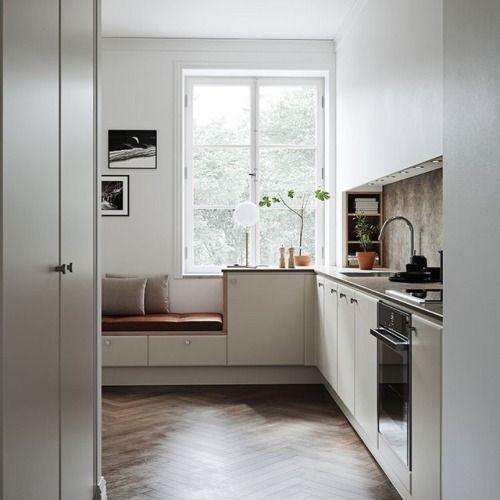 kitchen, wooden herringbone floor, white wall, white cabinet, brown backsplash, white floating cabinet, red cushion, glass window, white table lamp