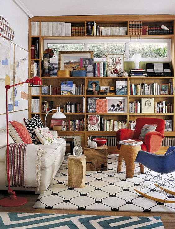 large wooden bookshelves with large hole near the top for windows, white wall, red floor lamp, wooden floor, white rug, white sofa, red and blue chairs, woden side table