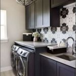 Laundry Room, Brown Floor, Off White Wall, Black Cabinet, Black Upper Cabinet, Patterned Backsplash, Black Laundry Machines, Black Framed Pendant