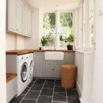 Laundry Room, Dark Floor, Grey Cabinet, White Wall, White Cabinet, White Machine, Rattan Basket, Wooden Counter Top, Wooden Bench, Windows