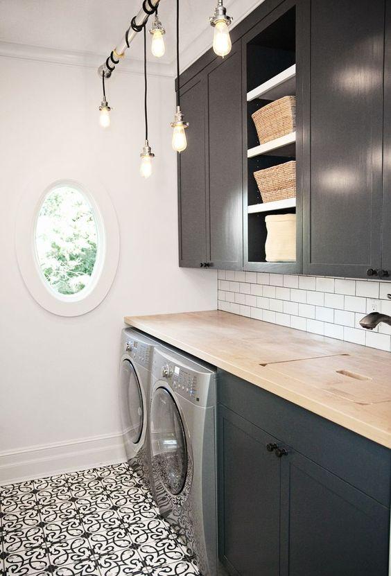 laundry room, patterned floor, white wall, white subway backsplash, black bottom cabinet, black upper cabinet, wooden counter top, golden pendants, round window