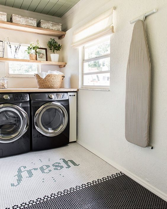laundry room, white black tiy hexagonal floor tiles, white wall, black machines, wooden counter top, wooden floating shelves, windows
