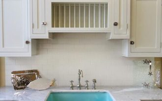 light blue sink, undermounted, white marble counter top, white subway backsplash, white cabinet, black marble counter