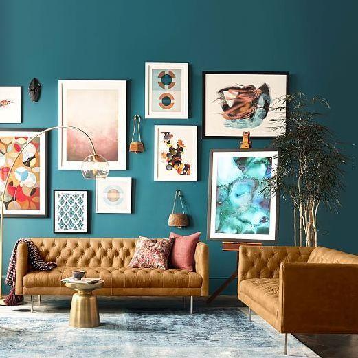 light orange sofas, golden low stool, teal wall, glass floor lamp, blue rug, grey seamless floor