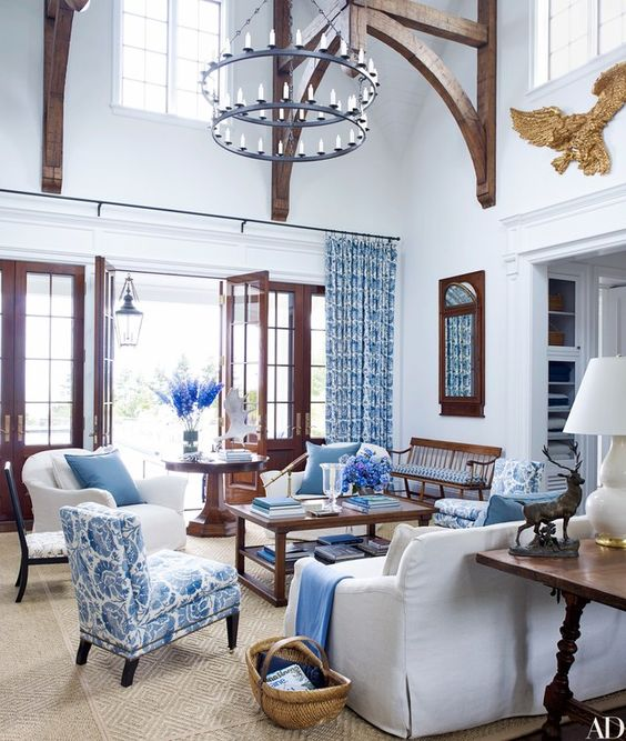living room, bron rug, coffee table, white wall, blue patterned curtain, blue patterned chair, white sofa, white chair, white table lamp, chandelier,
