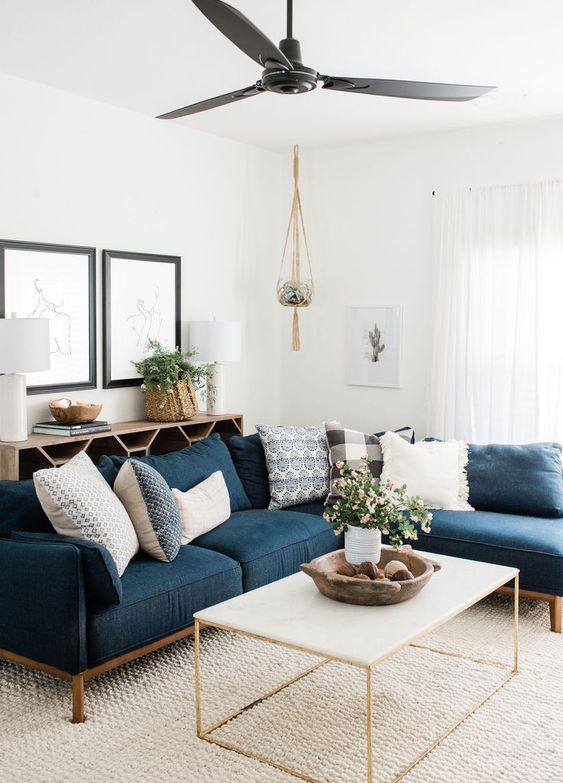 living room, brown rug, white wall, white coffee table, blue corner sofa, black ceiling fan
