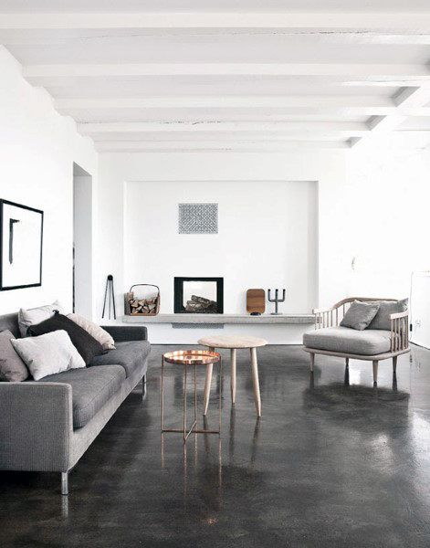 living room, dark concrete floor, white wall, white ceiling beams, grey sofa, grey chair, side table, grey floating shelves, fireplace