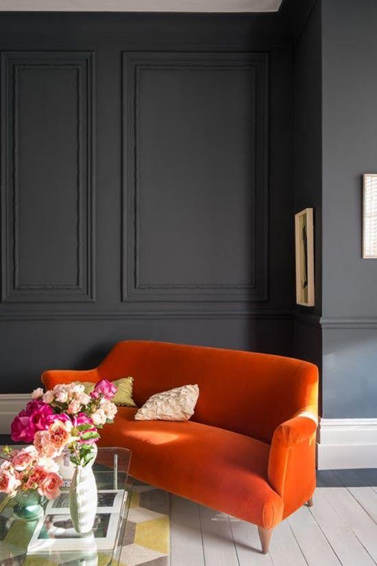 living room, dark grey wall, light wooden floor, bright orange sofa, glass top coffee table