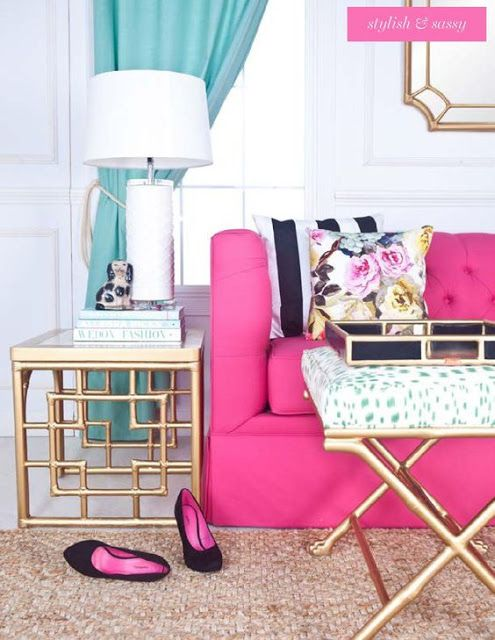 living room, grey floor, rattan rug, white wall, wainscoting, neon pink sofa, golden side table, white blue ottoman with golden cross legs