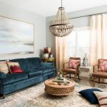 Living Room Patterned Rug, Navy Velvet Sofa, Round Brown Coffee Table, Rattan Chandelier, Brown Chairs