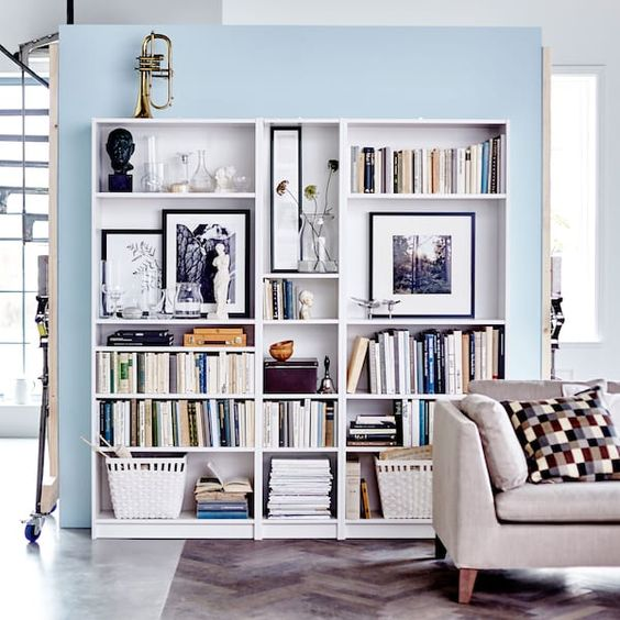 living room, seamless floor, blue wall, white shelves, grey sofa, pillows