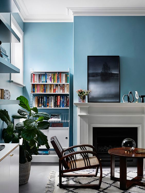 living room, white floor, blue wall, white fireplace, wooden round coffee table, wooden chairs, floating shelves