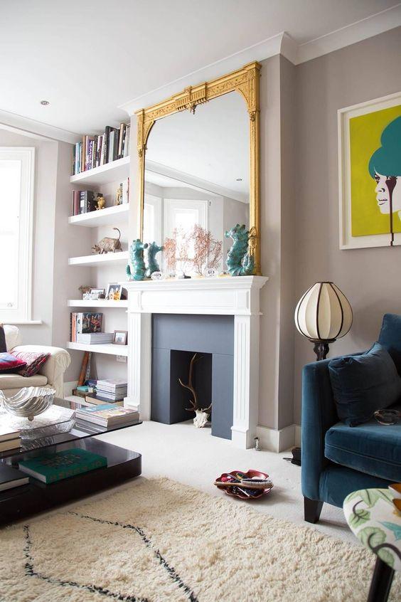 living room, white floor, white rug, cream wall, white floating shelves, white framed fire place, golden framed mirror, blue chair, white chair, coffee table with glass