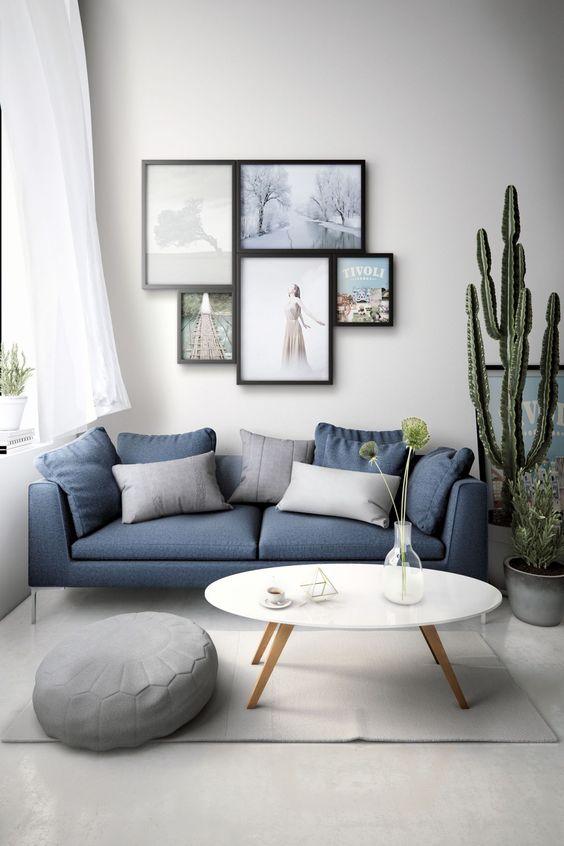 living room, white floor, white rug, white round modern coffee table, blue sofa, grey ottoman