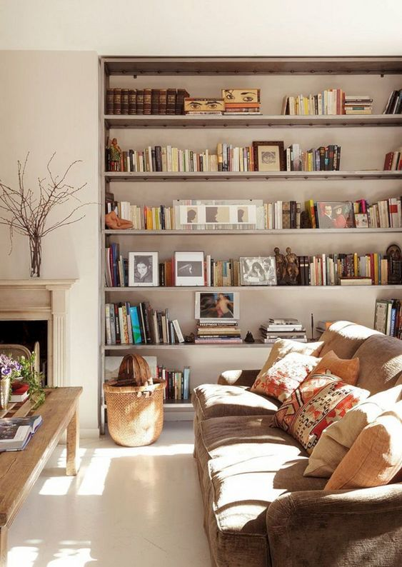 living room, white wall, white floor, brown sofa, shelves, wooden coffee table, fireplace