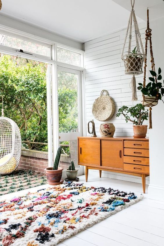 living room, white wooden floor, white wooden wall, brown wooden cabinets, rug, hanging pots, white rattan chair