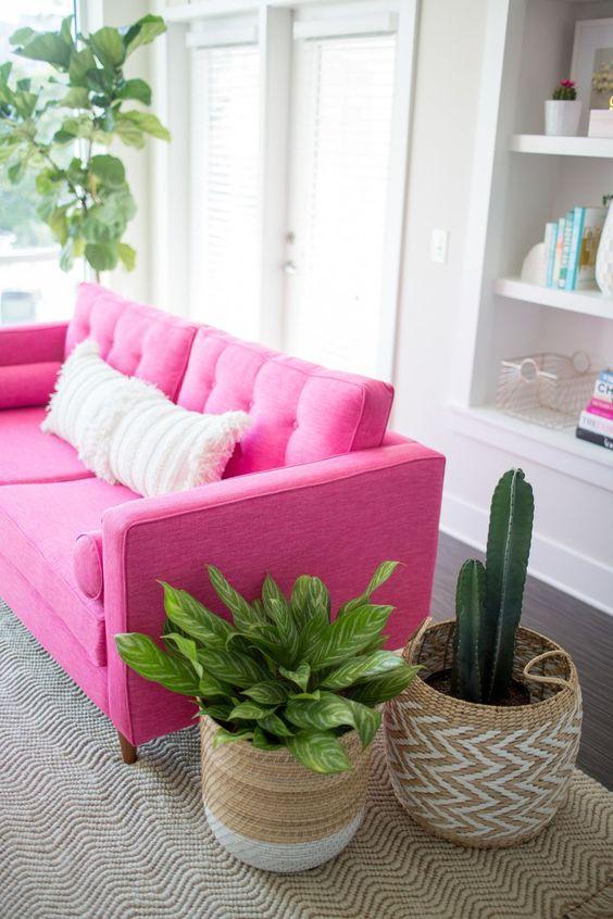 living room, wooden floor, brown rug, pink sofa, white built in shelves, white framed door