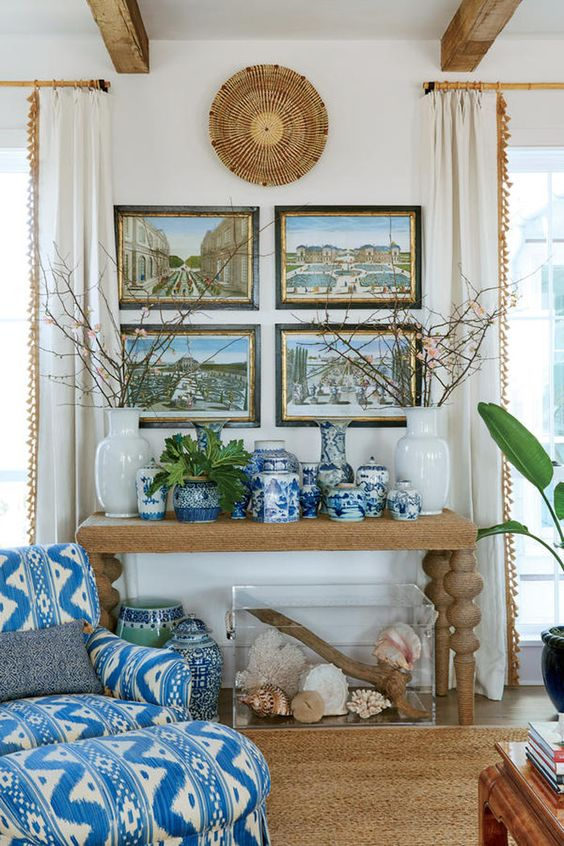 living room, wooden floor, brown rug, white wall, blue patterned lounge chair, paintings, wooden console table, wooden beams
