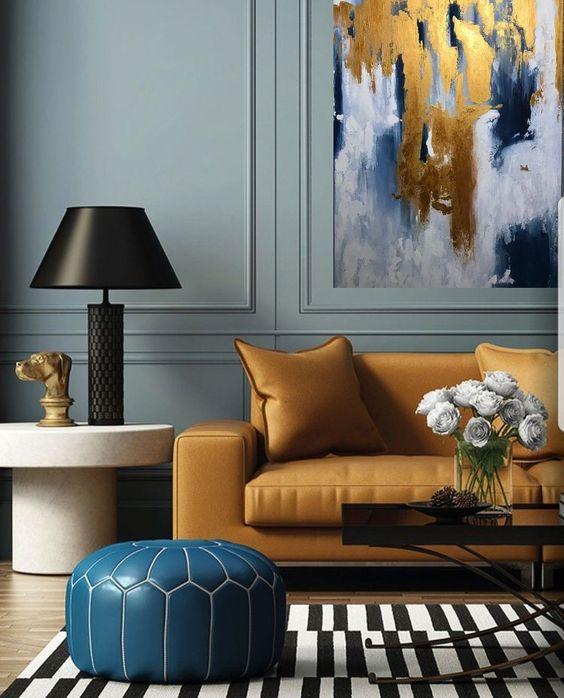 living room, wooden floor, green wall, white side table, light orange sofa, blue stools, striped rug, black coffee table