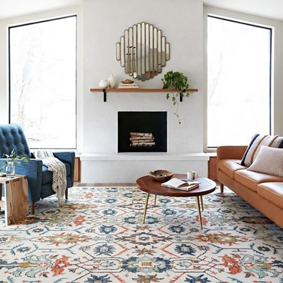 living room, wooden floor, patterned rug, round wooden coffee table, white wall, wooden floating shelves, blue tufted chair, brown leather sofa