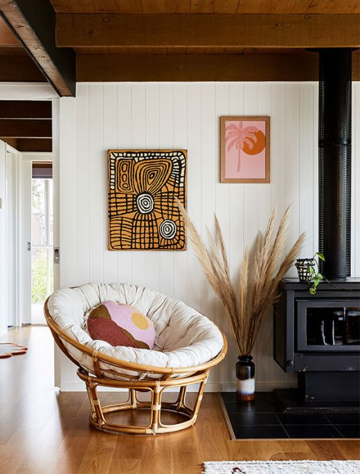 living room, wooden floor, white wall, black fireplace, roudn rattan chair with white cushion