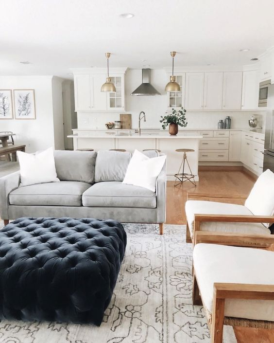 living room, wooden floor, wooden chairs with white cushion, grey sofa, patterned white rug, blue tufted ottoman