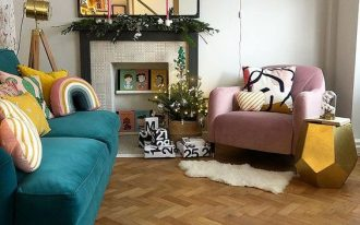 living room, wooden herringbone floor, white wall, green sofa, pink chair, mirror, fireplace