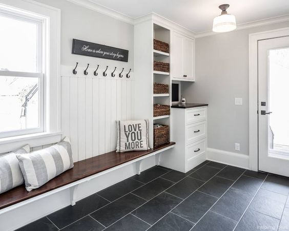 mudroom, black floor tiles, white wall, white shiplap wainscoting, floating wooden bench, white shlees with rattan basket, white cabinet