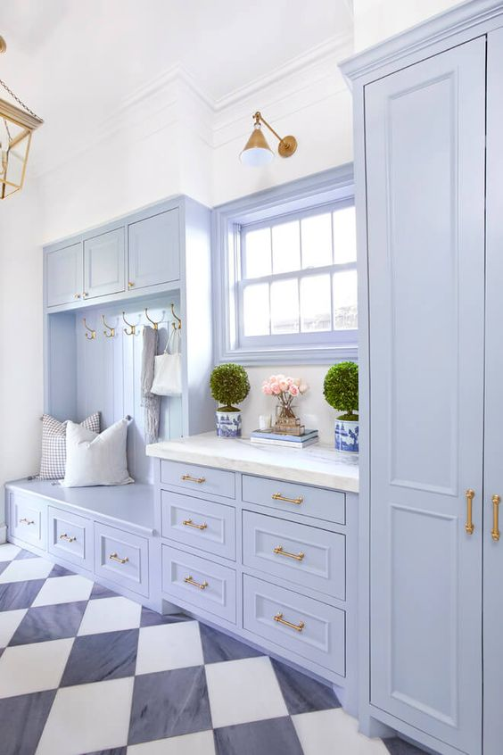 mudroom, black white plaid floor, white wall, blue wooden cabinet with bench, draers, white counter top, glass window, golden fixtures