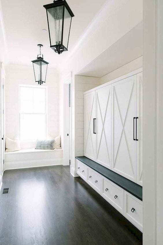 mudroom, black wooden floor, white shiplap, black pendant, white cupboard, white draewrs, dark bench, white window seat
