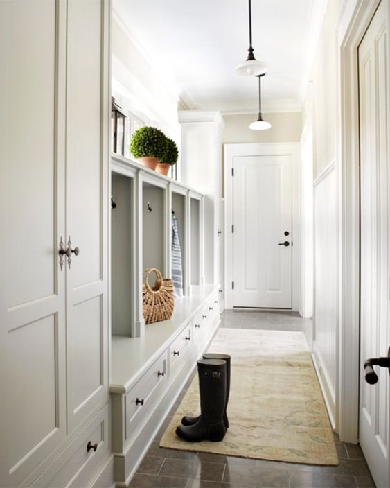 mudroom, brown marble, brown rug, white wooden cupboard, white pendant, white door