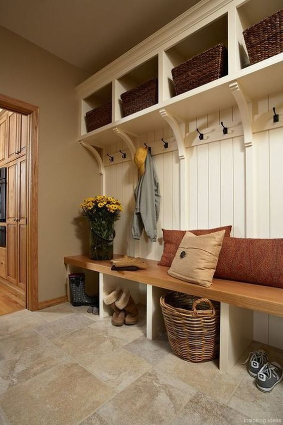 mudroom, brown marble floor, white wooden wall, white shelves on top, rattan basket, wooden bench with shelves