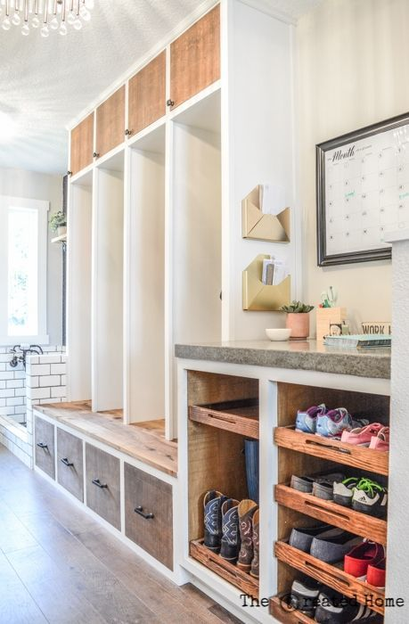 mudroom, wooden floor, wooden cupboard with tall section, drawers, wooden shoe rack, white wall, crystal chandelier