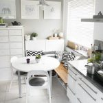 Nook, Grey Floor Tiles, White Round Table, White Chairs, Wooden Bench With White Shelves, White Wall, White Cabinet, White Cabinet With Grey Counter Top