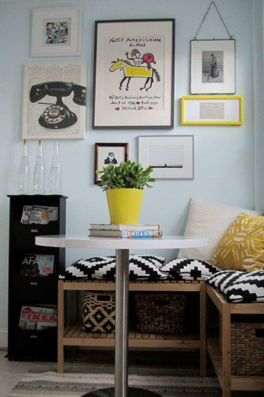 nook, light blue wall, wooden bench with rattan basket, white round table, black white pillows