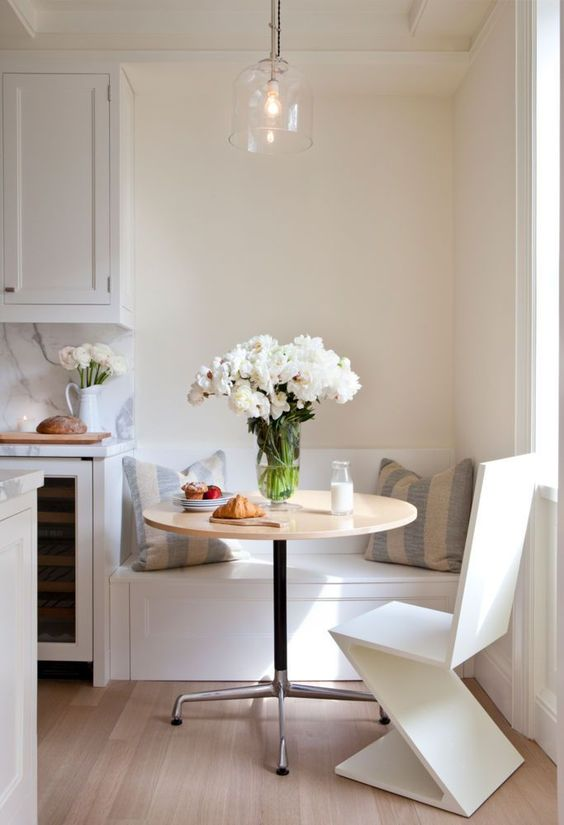 nook, light wooden floor, white wall, white bench, white chair, glass pendant