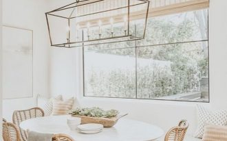 nook, white bench with drawers, white table, white rattan chairs, white wall, candle chandelier, glass window