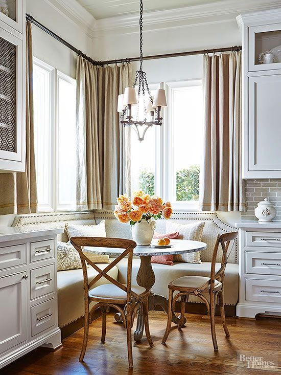 nook, wooden floor, white wall, white cabinet, off white corner sofa, wooden chairs, round table, white pendants.