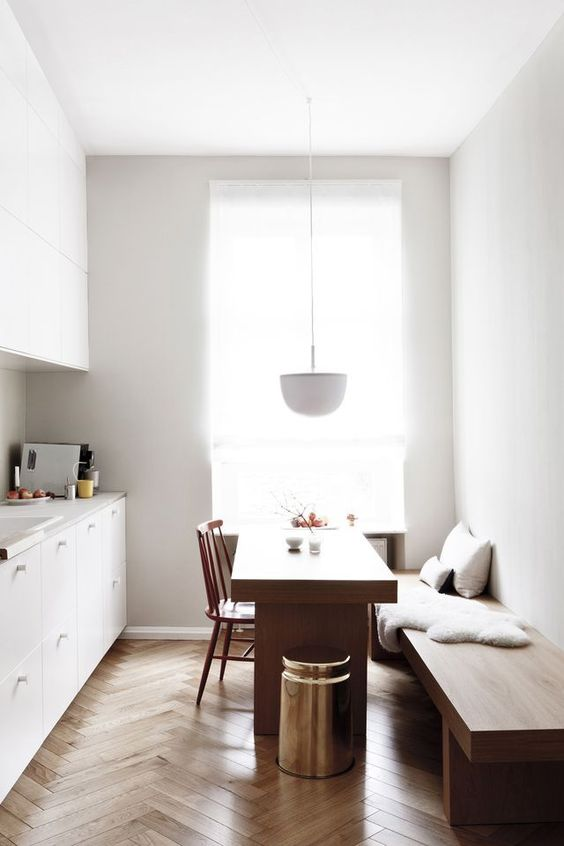 nook, wooden herringbone floor, white wall, white bottom cabinet, white counter top, white upper cabinet, white pendant, wooden bench, wooden table, wooden chair